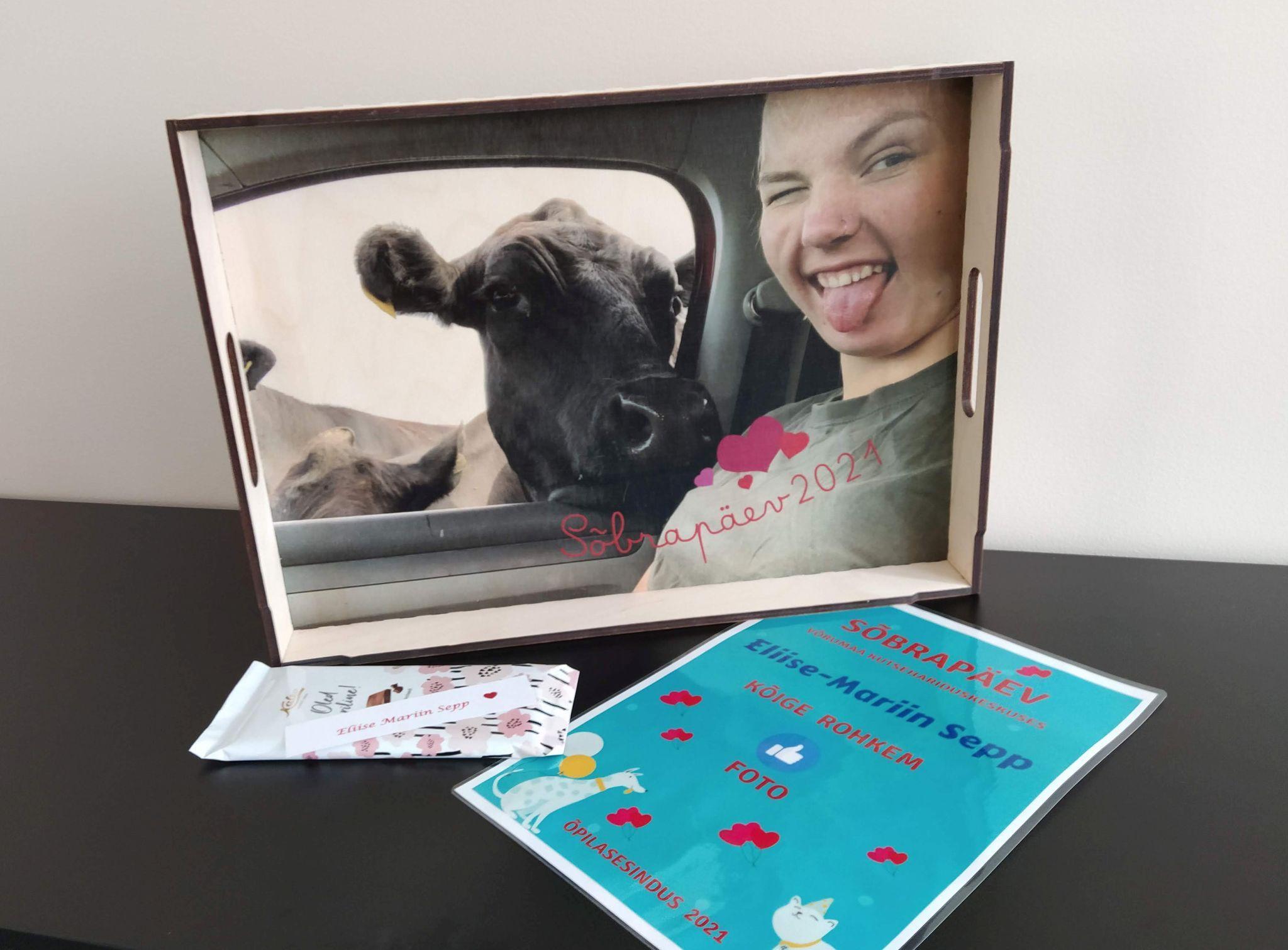 Fotokonkursi võidupilt trükitud puidust kandikule (Tüdruk lehmaga)