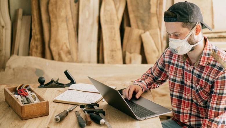 Mees puidutöökojas sülearvutiga