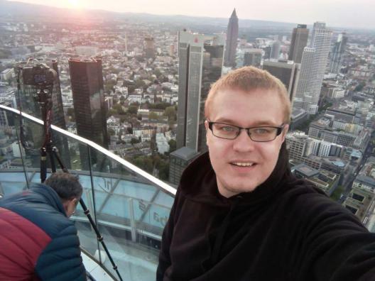 Mihkel teeb selfi katuselt (taustal pilvelõhkujad päikeseloojangus)